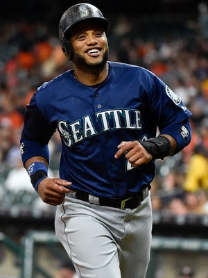 Mariners' Robinson Cano smiles after scoring a run on Nelson Cruz's single.