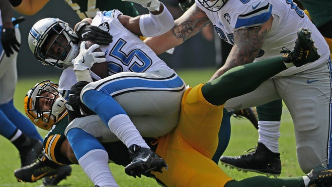 Lions RB Theo Riddick is hauled down by Packers linebacker Nick Perry at Lambeau Field on Sunday, Sept. 25, 2016.