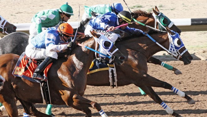 Jockey Jaime Leos (black cap) rode Carson City Girl (blue blinkers) to a narrow victory in Friday's $46,200 New Mexico Breeders' Stakes at SunRay Park and Casino in Farmington.