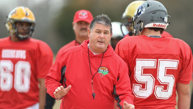 Former Southside and Wade Hampton coach Rick Scott, a member of six state championship teams as an assistant at Byrnes and Spartanburg, works with the South Carolina team during Shrine Bowl practice this week.