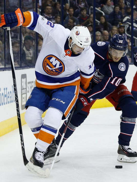 Columbus Blue Jackets' Alexander Wennberg, right, of Sweden, knocks the puck away from New York Islanders' Josh Bailey during the first period of an NHL hockey game Friday, Oct. 6, 2017, in Columbus, Ohio. (AP Photo/Jay LaPrete)