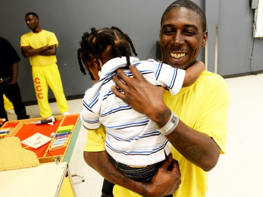 Tabiaus Russell gives his son a hug at the Caddo Correctional