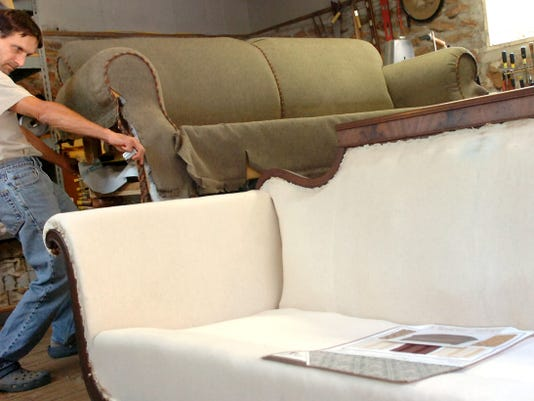 In this 2007 file photo, Jeff Lears of Shrewsbury Township takes a measurement of a sofa he is reupholstering at his business, Fieldstone Upholstery.