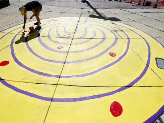 """Annalisa Gojmerac of Jackson Township paints what she calls a """"strawbale maze critterhop"""" on Continental Square in York. As part of their playful sidewalk initiative, Eat Play Breathe York has local artists creating permanent sidewalk mural/activities in York."""