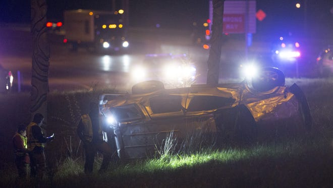 Investigators look over a fatal crash that happened about 9:15 pm, off eastboud I-70, at the offramp to Harding Road, that resulted in five people, none wearing seatbelts, ejected from this vehicle, Indianapolis, Tuesday, April 18, 2017. One person died at the scene, the other four were transported to area hospitals, two in serious condition.