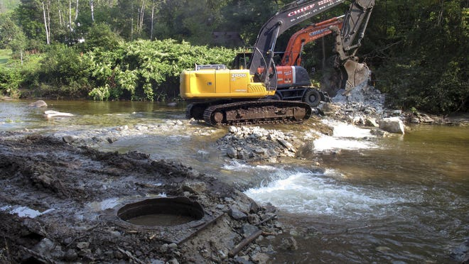 Two excavators remove an old dam Wednesday from the Wells River in Groton. The dam, built in 1909 and unused since 1927, was removed by the Connecticut River Watershed Council with help from state and federal agencies to improve fish habitat and make the river less prone to flooding.
