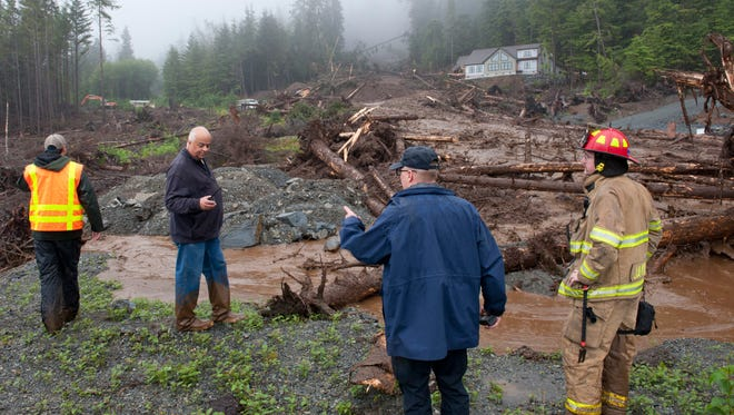From left, city engineer Dan Tadic, Fire Chief Dave Miller, Search and Rescue Capt. Lance Ewers, and firefighter Rob Janik look at the damage caused by a landslide Aug. 18, 2015 in SItka, Alaska.
