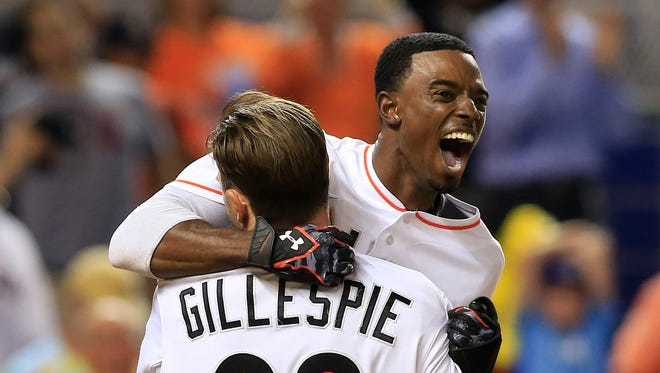 Dee Gordon celebrates with center fielder Cole Gillespie after scoring the winning run against the Red Sox.