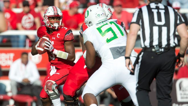 Utah Utes quarterback Troy Williams (3) drops back to pass as Oregon Ducks defensive lineman Gary Baker (51) rushes during the first half at Rice-Eccles Stadium.