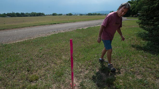 Fort Collins resident Steve Rumpler walks past a property line marker Friday in his front yard near the vacant field that Landmark Homes plans to build 479 homes on just northeast of Lemay Avenue and East Vine Drive in Fort Collins.
