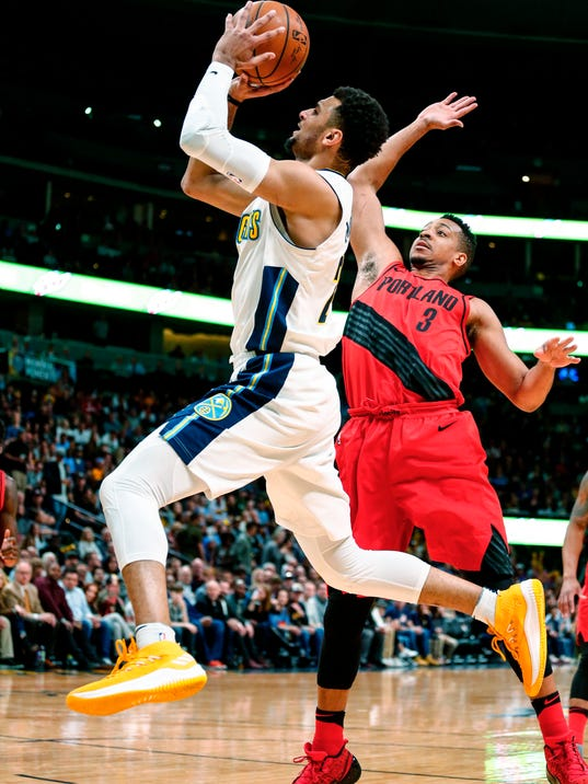 Denver Nuggets guard Jamal Murray (27) shoots against Portland Trail Blazers guard CJ McCollum (3) during the first quarter of an NBA basketball game Monday, April 9, 2018, in Denver. (AP Photo/Jack Dempsey)