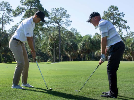 Erick Hidalgo practices his swing with Rob Churchill, Bonita Bay Club assistant pro, during The Immokalee Foundation's Inter-Club Challenge. Hidalgo is now a mentee of foundation board member John Costigan.