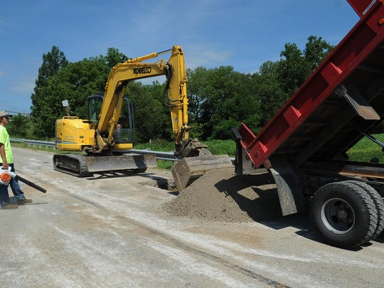 A Ross County Engineer's Office crew works on filling a sinkhole Tuesday on Kellenberger Road east of Ohio 104.