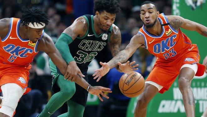 The Boston Celtics' Marcus Smart (36) battles Oklahoma City Thunder's Luguentz Dort (5) and Terrance Ferguson (23) for a loose ball during the second half of a March game, in Boston.