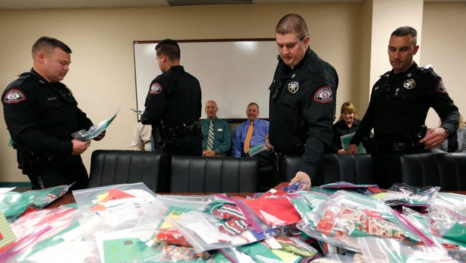 Greene County Sheriff's Deputies grab stockings stuffed treats from the Marine Corps League Auxiliary of SWMO 386 as part of Operation Santa for our Community Heroes as a gesture of good will and gratitude from the community on Tuesday, Nov. 15, 2016.