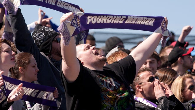 "Michael Price of Louisville raises a banner declaring himself a ""founding member"" as he shows support of his team, the Louisville City FC, during the opening game at Slugger field.