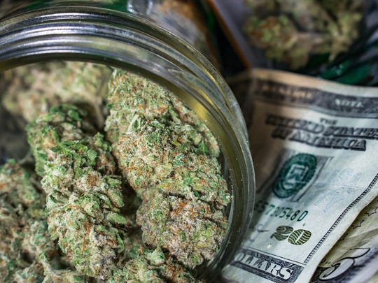 A clear jar packed with cannabis buds that's lying atop a small pile of cash.