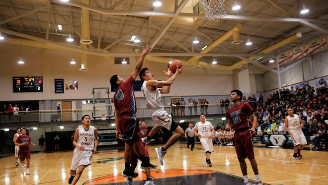 Navajo Prep's Trejan Clichee drives for for a layup attempt against Shiprock's Kieon Harvey, No. 10, during the first quarter of Thursday's District 1-4A opener in Farmington. Visit daily-times.com for the latest sports video highlights, photo galleries and basketball scores.