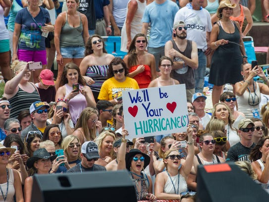 Fans listen to Luke Combs as he performs on the Riverfront
