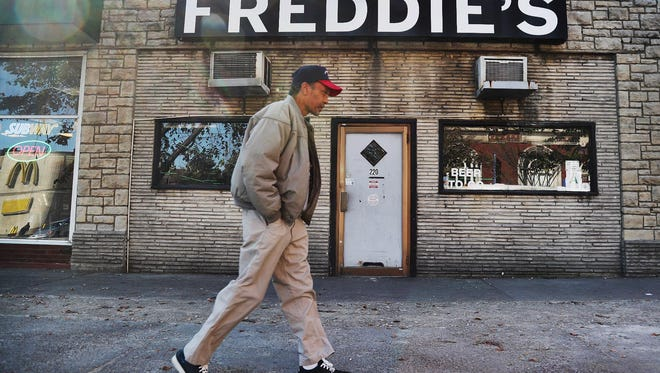 A man walks by the now-closed Freddie's Bar and Lounge at 220 E. Broadway. But owner Freddie Scarlott says he'll reopen.