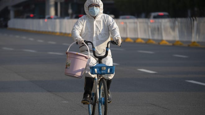 A resident wearing mask and suit against the coronavirus cycles in Wuhan in central China's Hubei province on Sunday, April 12, 2020. For most people, the new coronavirus causes only mild or moderate symptoms. For some it can cause more severe illness.