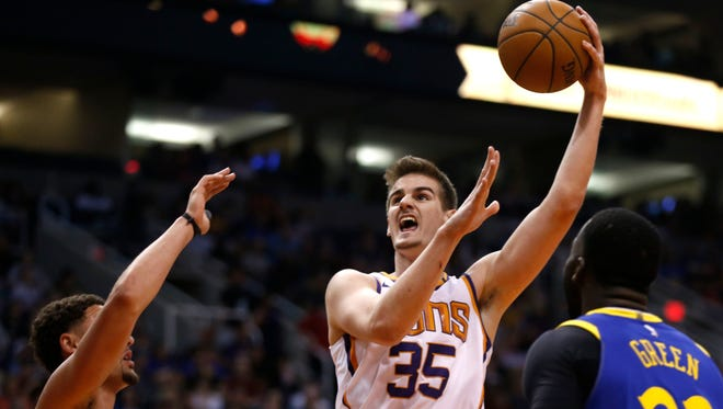 Suns Dragan Bender (35) shoots a hook shot against the Warriors Klay Thompson (11) and Draymond Green (23) during the second half at Talking Stick Resort Arena in Phoenix, Ariz. on April 8, 2018.