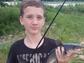 Caleb MacKnett holds a white catfish he caught while