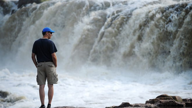 Tom Goodrich, of Rapid City, looks on as the Big Sioux River surges over the falls at Falls Park in 2015.