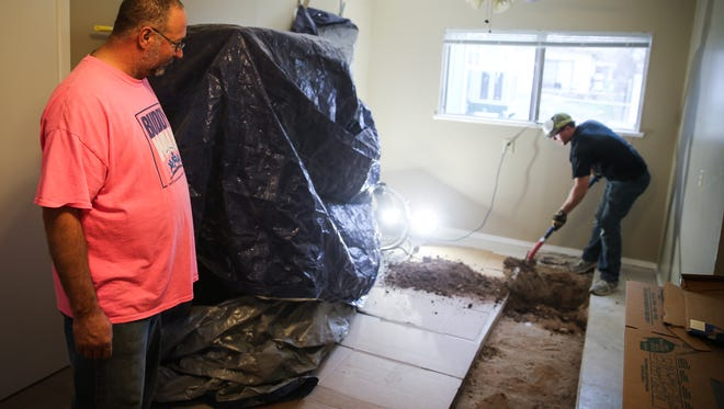 Rodney Brown checks on work as Drew Fulfer, a Freedom Home volunteer, digs out a trench for the plumbing to be replaced Saturday, March 17, 2018, at Connie Motley's home.