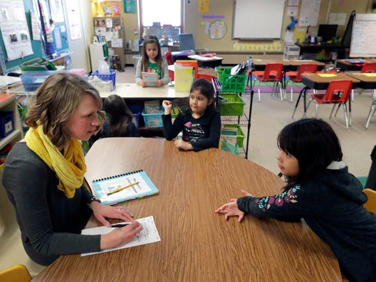 First-grade teacher Emily Thomas (left) works on an oral language group with students Lizbeth Garcia Vera and Stephanie Lopez Rivera (right) on Monday at Horizons Elementary School in Appleton. Horizons is part of a state program to reduce class sizes.
