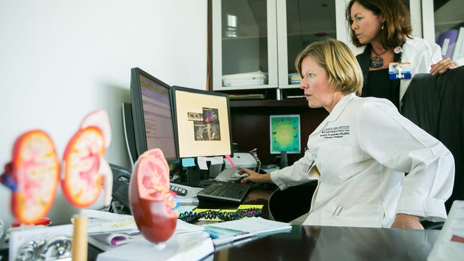 Transplant Administrator Brandi Krushelniski, bottom, and Kidney Transplant Program Specialist Lisa Scharnow look over x-rays of diseased kidneys at Krushelniski's office at the Norton Thoracic Institute at St. Joseph's Hospital and Medical Center in Phoenix on Monday, July 14, 2014.