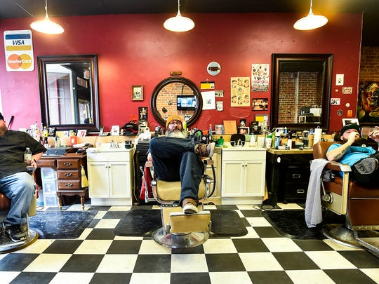 The cutting crew at Nathan's Barber Shop in downtown Marion takes a break in between serving customers on Monday. The shop opened its doors to local men in need, giving free haircuts to those who didn't have the finances available. From left to right, Ben Meade, Ian Cooper and shop owner Nathan Riddle.