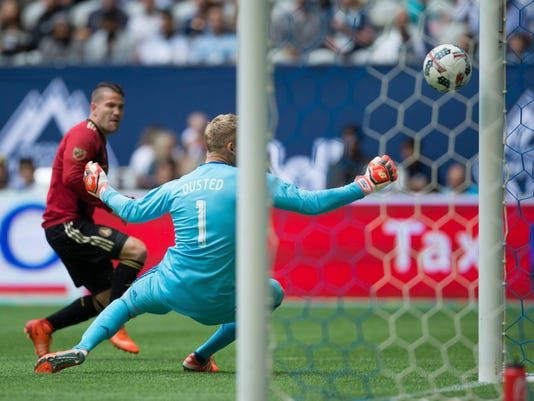Atlanta United's Greg Garza, back left, scores against Vancouver Whitecaps goalkeeper David Ousted during the first half of an MLS soccer match in Vancouver, British Columbia, Saturday, June 3, 2017. (Darryl Dyck/The Canadian Press via AP)