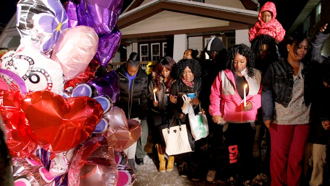 Family and friends hold a candlelight vigil Tuesday for Melanie Johnson, 15, who died Monday night when gunfire struck her home on N. 35th St. near W. Silver Spring Drive.