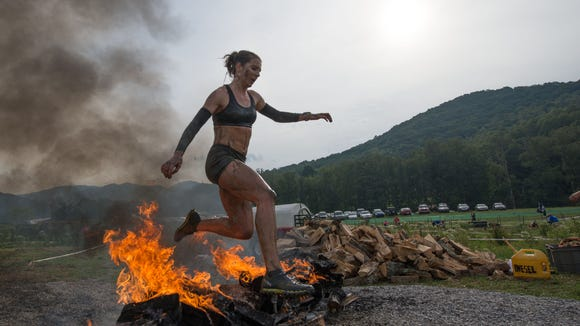 Women's first-place finisher Janet Barry leaps over the log obstacle at the end of the 2015 Spartan Race. The endurance race returns to Asheville July 29 and 30.