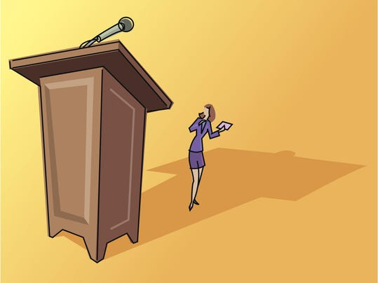 Small businesswoman overshadowed by large lectern