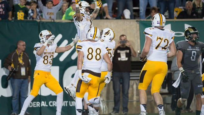 Wyoming players celebrate a touchdown late Saturday night during the Cowboys' 38-17 win over CSU in the Border War football game at Hughes Stadium.