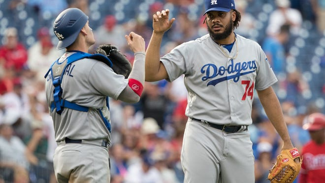 Closer Kenley Jansen, right, and catcher Yasmani Grandal celebrate after the Dodgers beat the Phillies 5-4 in Philadelphia on Thursday to avoid a four-game sweep.