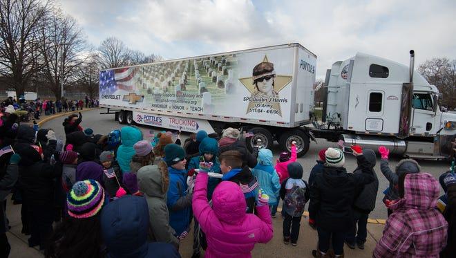 Students at Silver Lake Elementary School in Middletown wave U.S. flags as the Wreaths Across America caravan departs their school.