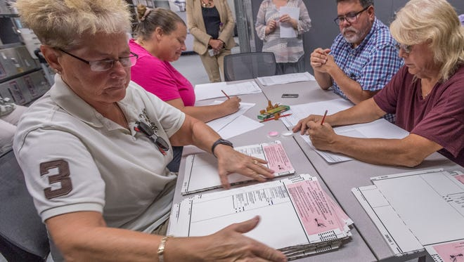 Volunteers Judy Morphis, left, Veronica Holmes, Chris Saenz and Bobbie Jo Mendez manually recount ballots from the July 11 recall election Tuesday. Ballot counts from election day recalled Dr. Parmod Kumar from the Tulare Regional Medical Center Board of Directors. Candidate Senovia Gutierrez was elected to replace him.