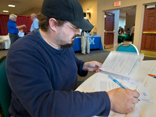 Geoff Lobdell looks over paper work at a job fair hosted by the IBM Burlington at the Sheraton Hotel and Conference Center in South Burlington on Friday.