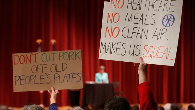 Audience memners hold up signs as Sen. Joni Ernst takes the stage Friday, March 17, 2017, during her Polk Count town hall meeting in Sheslow Auditorium at Drake Universtiy.