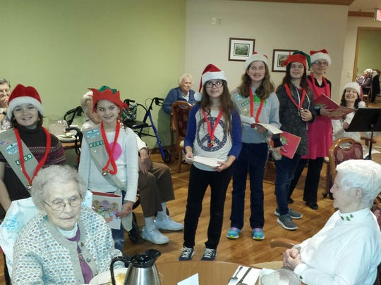 Pictured are Ari Hilsabeck, Dakota Stewart, Kayley Bell, Callie Kraemer, Miranda Gregory, Justyna Henke and Gwen Gregory accompanying with her flute. Resident Arlene made the red bell necklaces the girls are wearing a couple years back. They enjoy visiting with them each year with song, cookies and smiles.