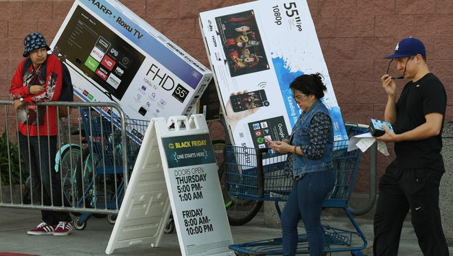 """Shoppers wait their TV's during the """"Black Friday"""" sales at a Best Buy store in Culver City, Calif., on November 25, 2016."""
