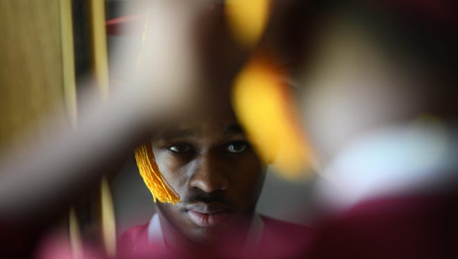 Kedanta Chandler adjusts his graduation cap in a mirror at his home in Melfa, Va. on Thursday, June 11, 2015. Chandler became the first black male valedictorian to graduate in Nandua High School's history. He will attend Virginia Polytechnic Institute and State University in the fall to study engineering.