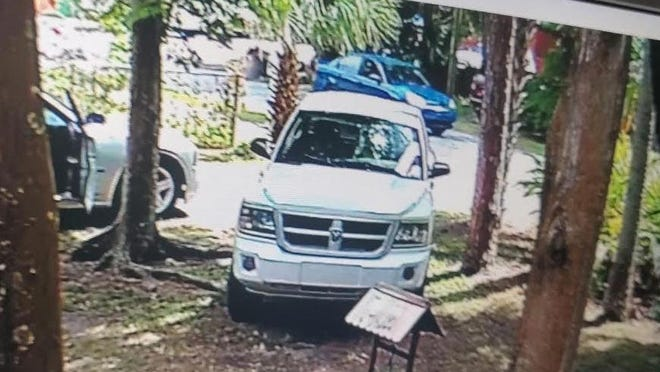 Holly Hill Police are looking for two men in the small blue car in the background of this photo. The men are sought for questioning in the shooting of a woman on Sunday.