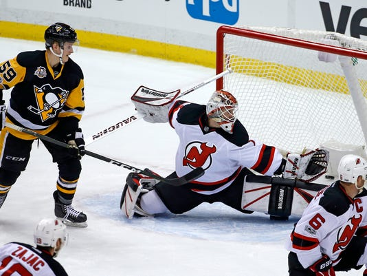 A shot by Pittsburgh Penguins' Sidney Crosby gets behind New Jersey Devils goalie Keith Kinkaid for a goal in the first period of an NHL hockey game in Pittsburgh, Friday, March 17, 2017. (AP Photo/Gene J. Puskar)