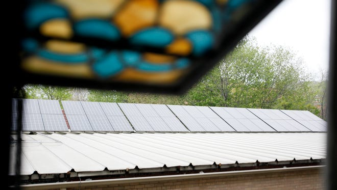 The Earth Team at First Congregational United Church on Oak Street installed solar panels at the church in 2011, seen here through a stained glass window April 18, 2017.