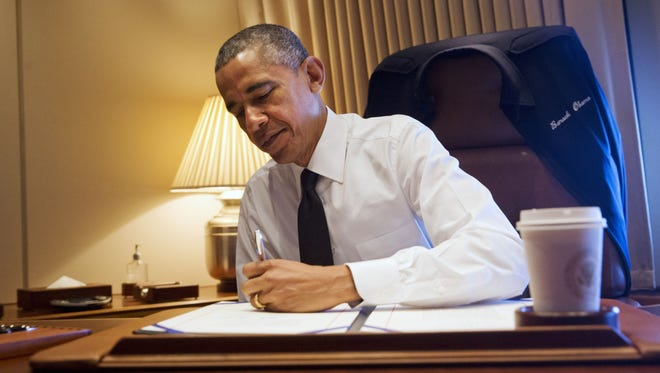 "President Barack Obama signs legislation awarding a Congressional Gold Medal to the people who participated in the ""Bloody Sunday"" march, Turnaround Tuesday, or the final Selma to Montgomery Voting Rights March in March of 1965, at his desk aboard Air Force One Saturday, March 7, 2015. The president was en route to Selma, Ala., to attend the 50th Anniversary of ""Bloody Sunday,"" which refers to the day in 1965 when police attacked marchers demonstrating for voting rights. (AP Photo/Jacquelyn Martin)"