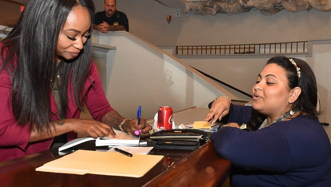 Mimi Crown autographs a copy of her book following her talk Tuesday at the Delta Grand.